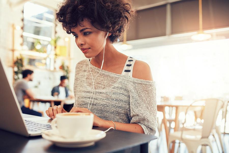 Woman using free WiFi in restaurant
