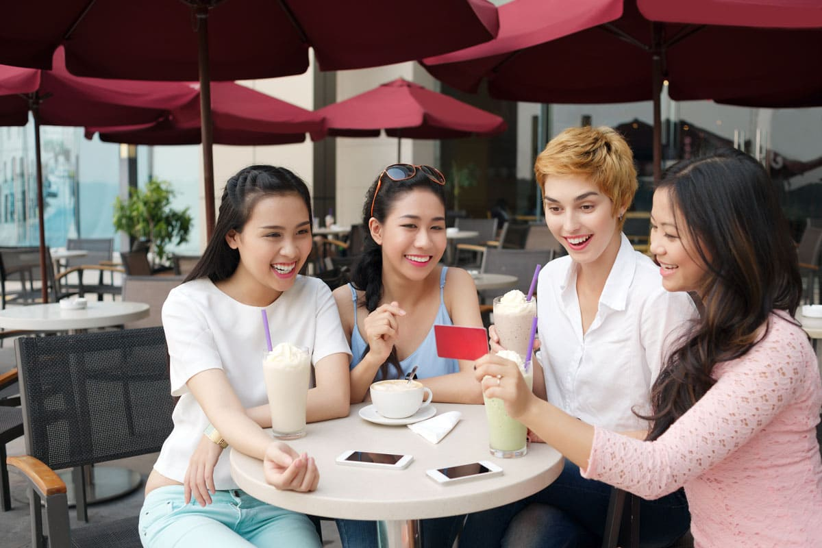 group of friends using gift card at cafe